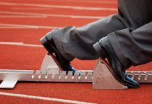 businessman in starting blocks on running track
