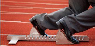 businessman in starting blocks on running track