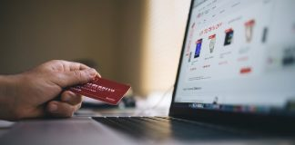 man holding credit card in front of monitor