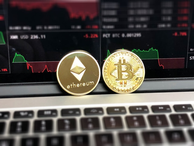bitcoin and ethereum coins on laptop